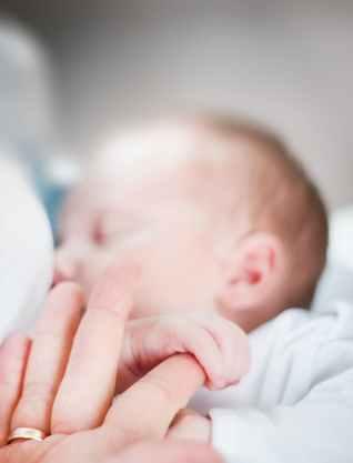 tilt shift lens photo of infant s hand holding index finger of adult